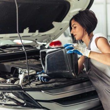 lady pouring transmission fluid into car